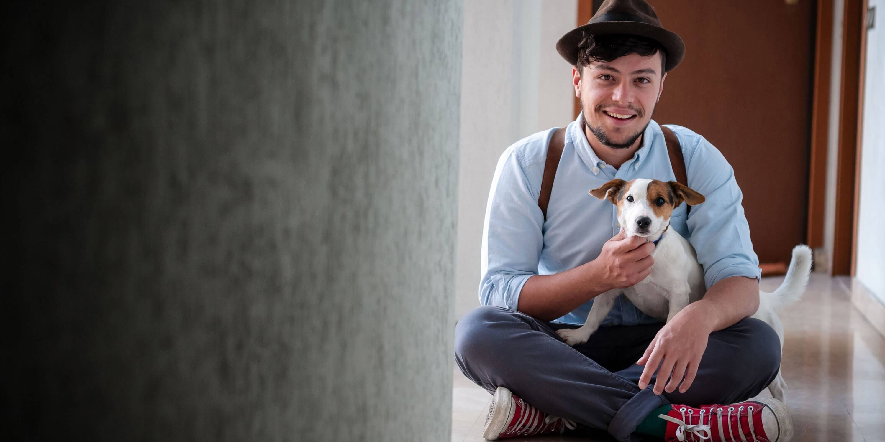 hipster young man posing with jack russell dog